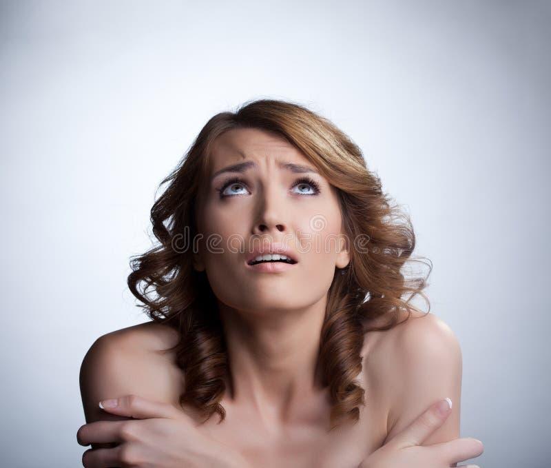 Erschrockene junge Frau, die oben schaut lizenzfreies stockfoto