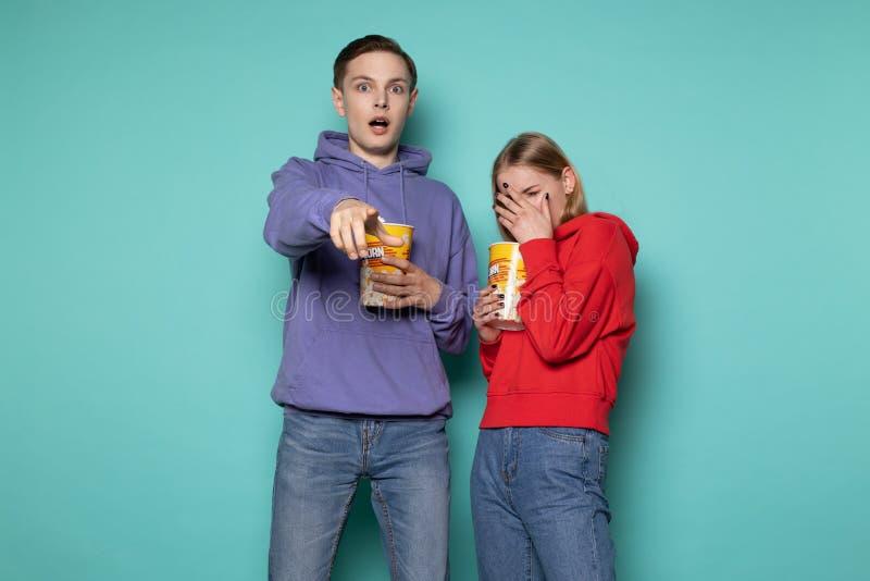 Erschrockene junge Paare in der zuf?lligen Kleidung, die Popcorn isst lizenzfreie stockfotos