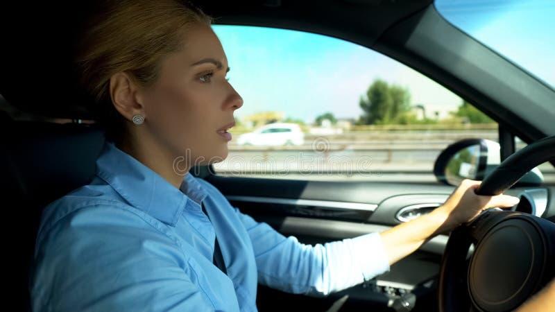 Erschrockene sorgfältig fahrende Frau, Problemsituation auf Straße, Risiko des Autounfalls lizenzfreie stockbilder