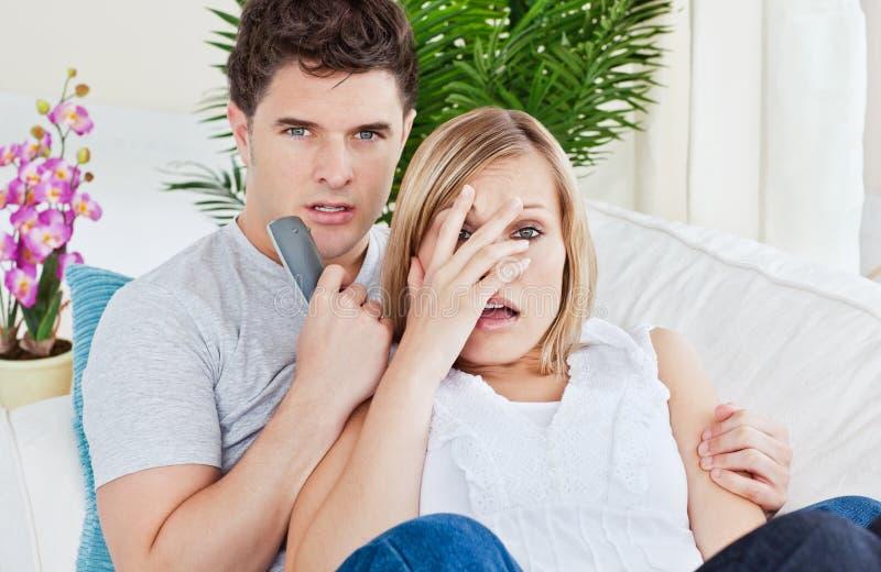 Erschrockener überwachender Horrorfilm der Paare, der auf Sofa liegt lizenzfreie stockfotos