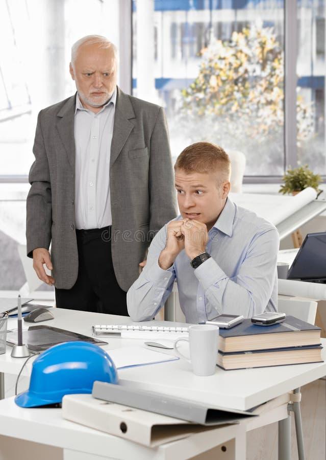 Erschrockener Büroangestellter mit verärgertem Leitprogramm stockbilder