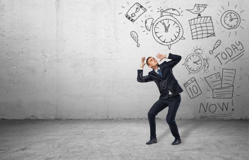 Erschrockener Geschäftsmann, der mit seinen Händen von den Zeichnungen von Kalendern und von Uhren sich abschirmt stockfotos