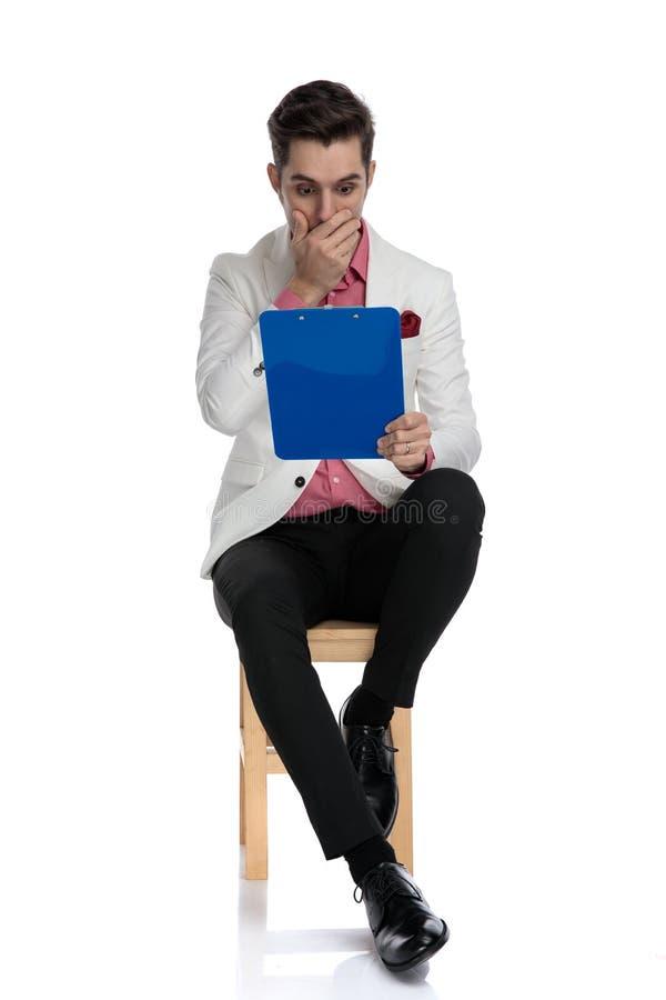 Erschrockener junger Geschäftsmann, der schlechte Nachrichten auf einem Klemmbrett sitzt und erading lizenzfreies stockbild