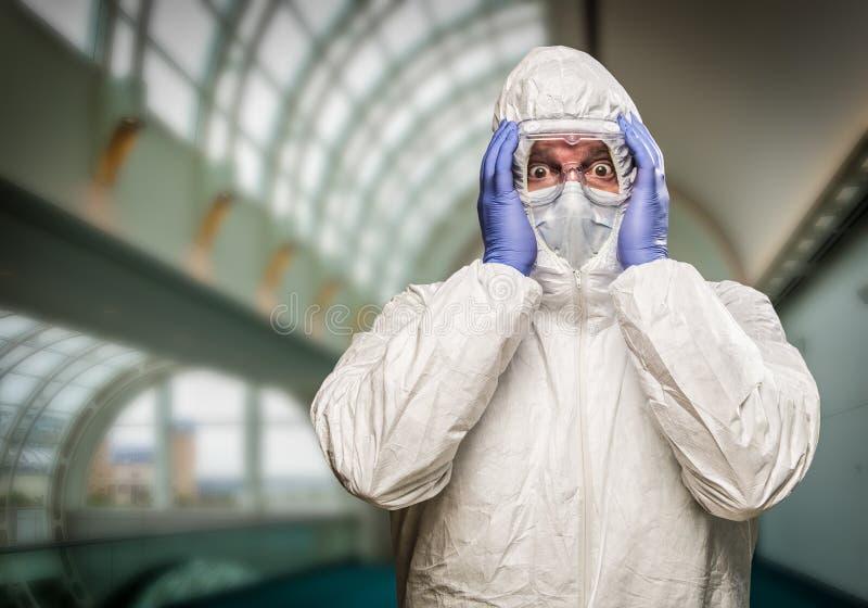 Erschrockener Mann halten Haupt mit den Händen, die HAZMAT-Schutzanzug tragen stockbild