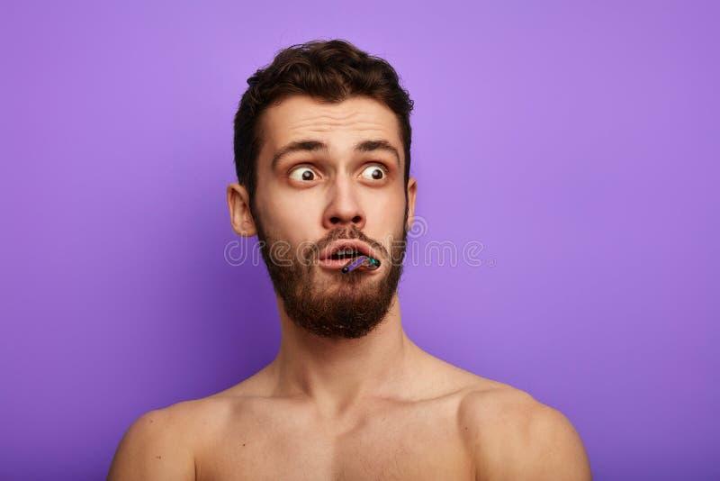 Erschrockener Mann mit der Zahnbürste, die Schock und volle Ungläubigkeit ausdrückt lizenzfreie stockbilder