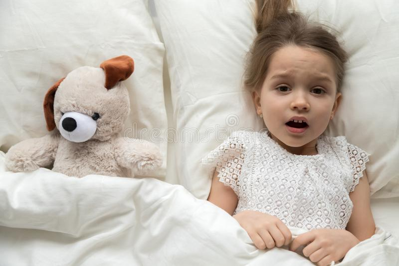 Erschrockenes Kind, das im Bett mit dem Spielzeug ängstlich vom Albtraum liegt stockbild