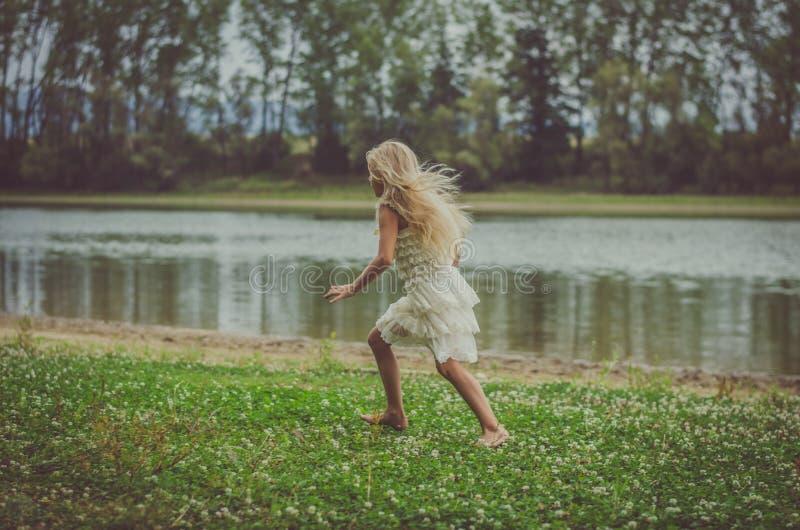 Erschrockenes Kind, das weg in die Natur an der dunklen Atmosphäre läuft lizenzfreie stockfotos