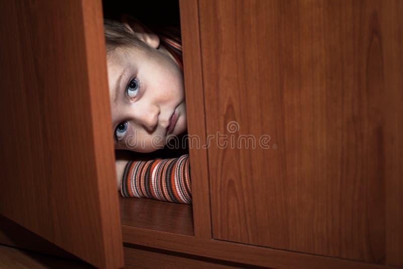 Erschrockenes Kinderverstecken lizenzfreie stockfotografie