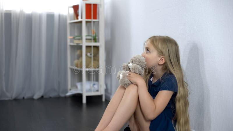Erschrockenes Mädchen mit dem Spielzeugfreund, der auf dem Boden, erschrocken vom eingebildeten Monster sitzt stockfotos