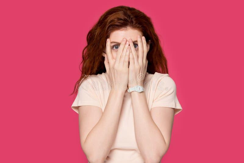 Erschrockenes Rothaarigemädchen-Abdeckungsgesicht, das durch Finger späht stockfoto