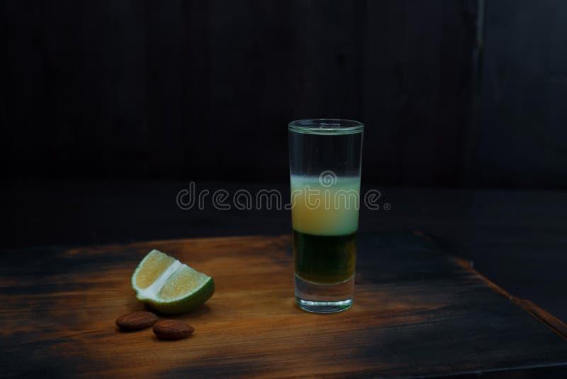 Erstaunliche alkoholische süße Zweischicht auf dem Tisch geschossen mit Wodka- und Fruchtsirupständen in der Stange lizenzfreies stockbild