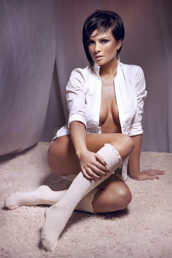 Erstaunliche Brunettedame, die im weißen Hemd sitzt stockfoto