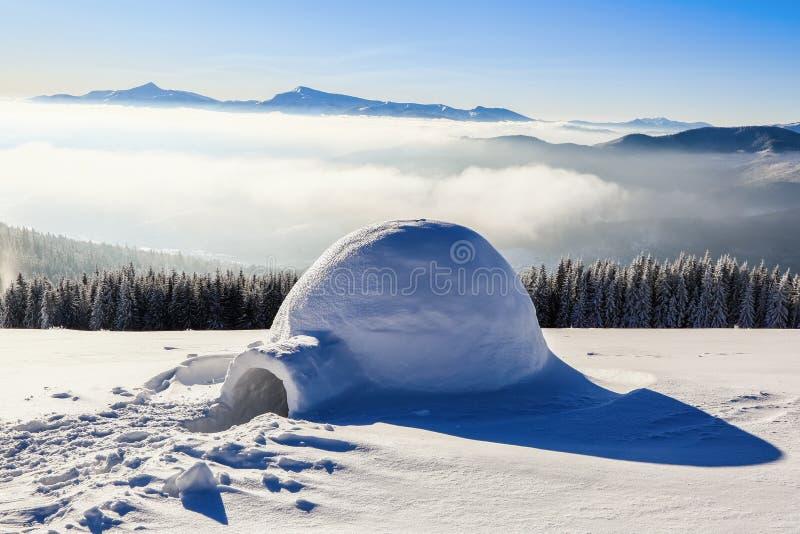 Erstaunliche enorme weiße schneebedeckte Hütte, Iglu, den das Haus des lokalisierten Touristen auf hohem Berg steht lizenzfreie stockfotografie