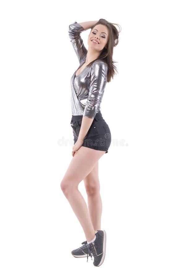 Erstaunliche Frau im glänzenden silbernen Hemd und kurze Hosen, die mit der Hand im Haar aufwerfen und an der Kamera lächeln stockfotografie