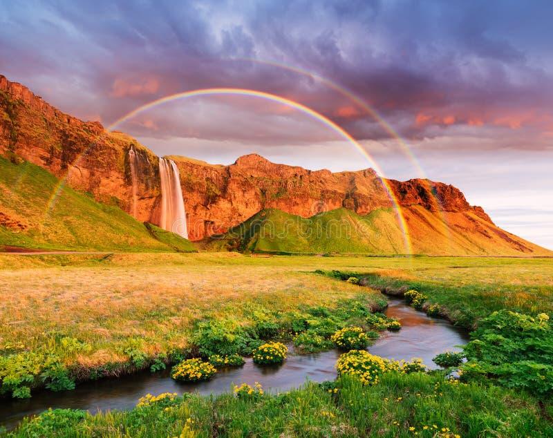 Erstaunliche Landschaft mit einem Regenbogen und einem Wasserfall in Island lizenzfreies stockbild