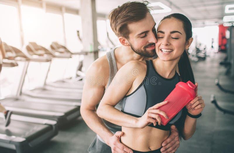 Erstaunliche Paare, die in der Turnhalle stehen Der Kerl umarmt seine Freundin Sie schaut glücklich Abschluss oben Schneiden Sie  lizenzfreie stockfotografie