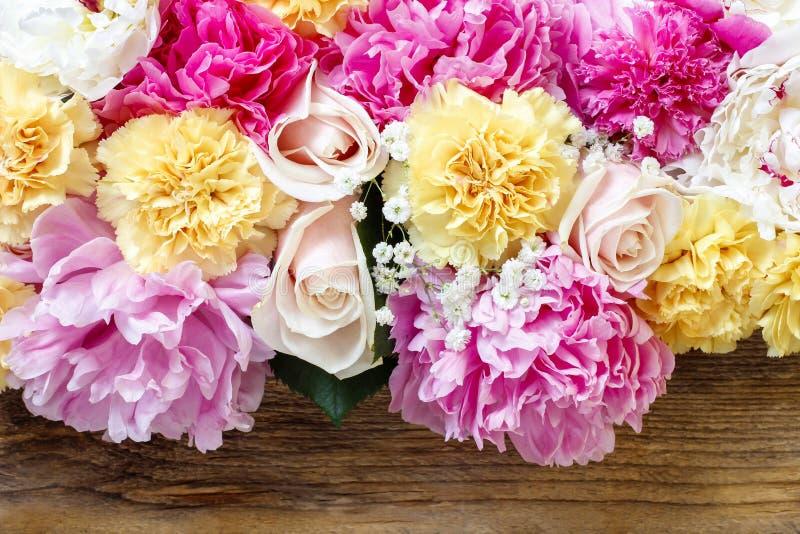 Erstaunliche rosa Pfingstrosen, gelbe Gartennelken und Rosen lizenzfreie stockbilder
