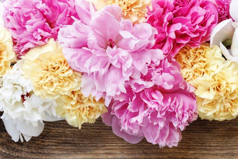 Erstaunliche rosa Pfingstrosen, gelbe Gartennelken und Rosen stockbild
