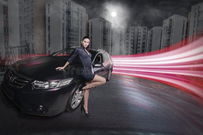 Erstaunliche Schönheitsfrau, die nahe bei ihrem Auto aufwirft stockfotografie