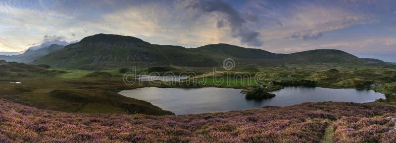 Erstaunliche Sonnenaufgangpanoramalandschaft von Heide mit Gebirgslak stockbild