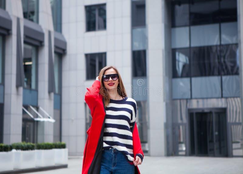 Erstaunliche Zauberblondine in der modischen Ausstattung, die gegen den städtischen Hintergrund der Wand, Modeporträt des Modebli stockfoto