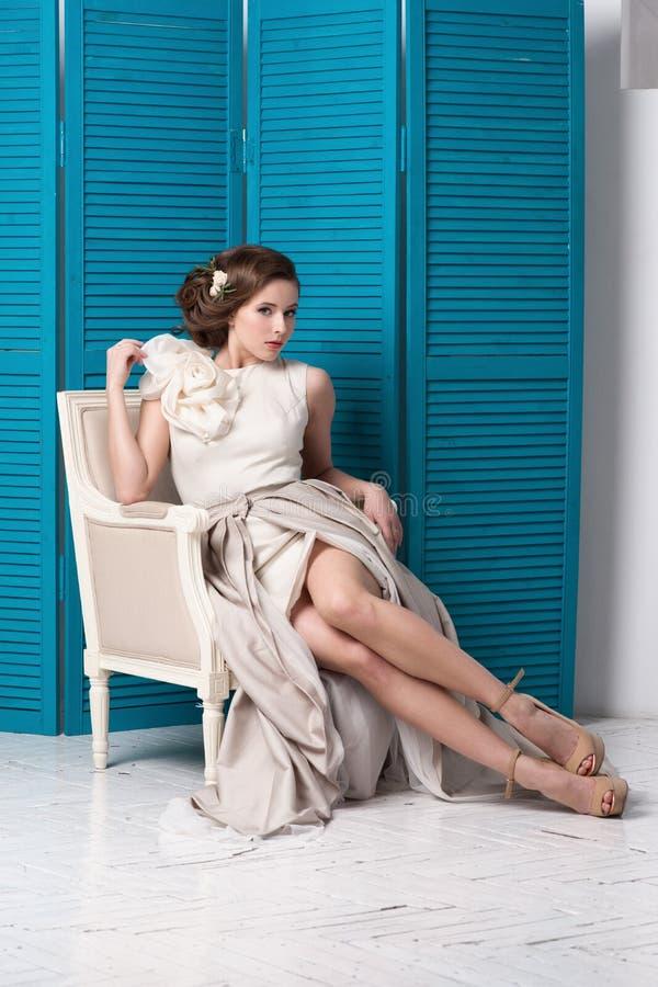 Erstaunlicher Brunette, der auf Stuhl aufwirft stockfotografie