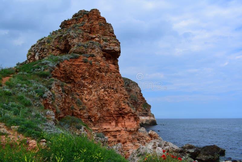 Erstaunlicher großer roter Felsen über dem Meer lizenzfreie stockfotos
