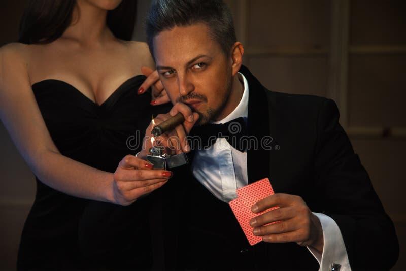 Erstaunlicher moderner Mann mit der Zigarre, die Poker spielt stockfotos