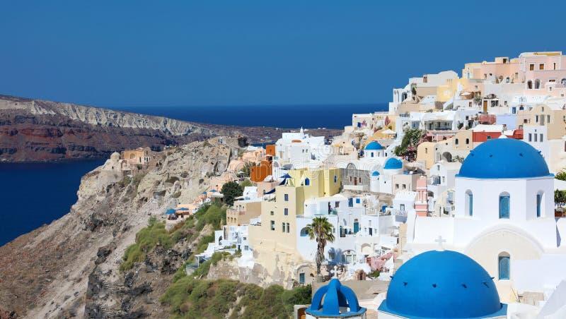 Erstaunlicher Panoramablick von Santorini-Insel mit weißen Häusern und blauen Hauben auf berühmtem griechischem Erholungsort Oia, stockfoto