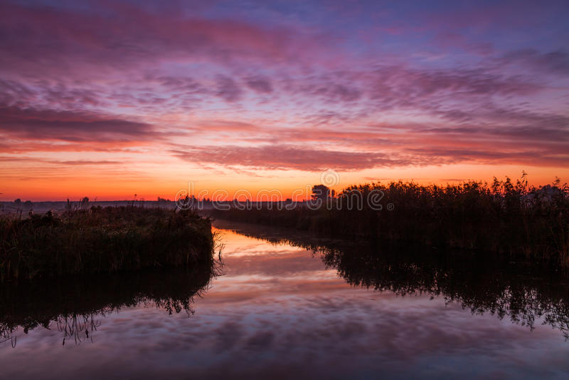 Erstaunlicher purpurroter Sonnenaufgang über Fluss stockfotografie