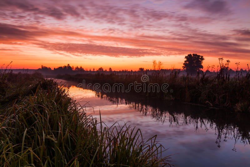 Erstaunlicher purpurroter Sonnenaufgang über ländlichem Fluss stockbild