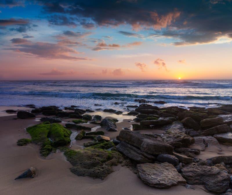 Erstaunlicher Sonnenuntergang auf dem Ozean Ansicht des drastischen bewölkten Himmels und der steinigen Küste Portugal lizenzfreie stockfotografie