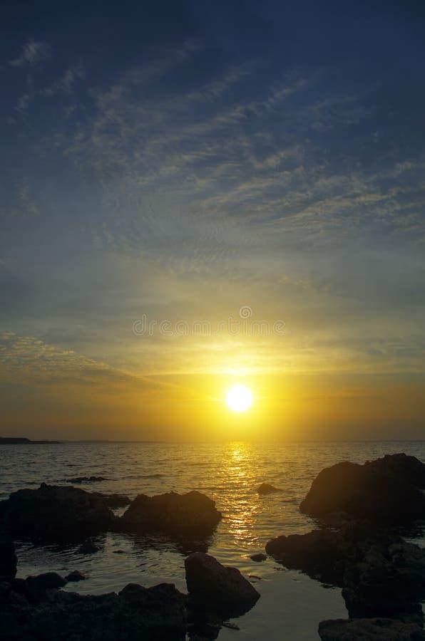 Erstaunlicher Sonnenuntergang auf einem felsigen Strand lizenzfreies stockbild