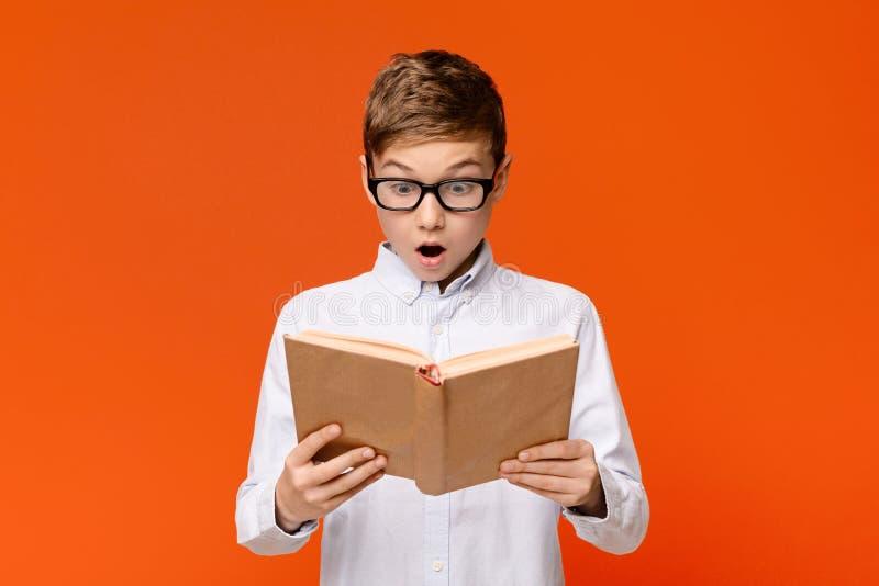 Erstaunlicher Teenager-Nerd in Gläsern emotional beim Lesen des Buches lizenzfreie stockfotos