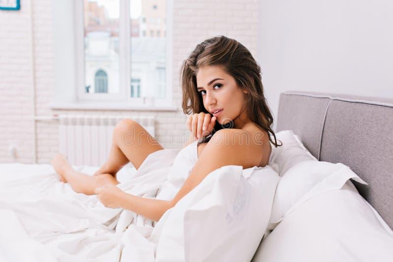 Erstaunliches reizend Mädchen mit dem langen brunette Haar, das im weißen Bett in der modernen Wohnung kühlt Sexy Blick, positive lizenzfreie stockbilder