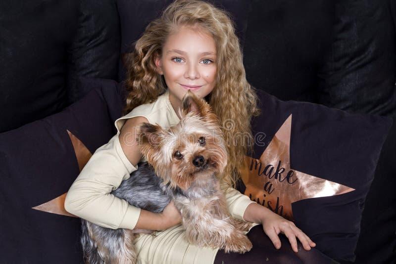 Erstaunliches schönes kleines Mädchen mit dem langen blonden Haar liegt auf der Bettwäsche in den Druckhunden und liegt nahe bei  lizenzfreie stockfotos