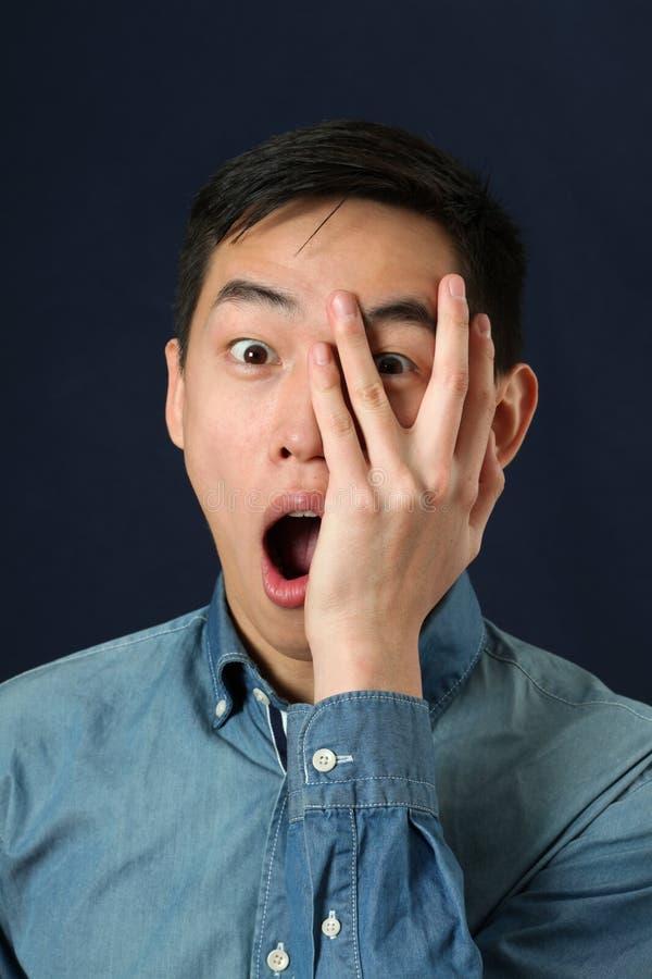 Erstaunter junger asiatischer Mann, der durch seine Finger schaut lizenzfreies stockfoto