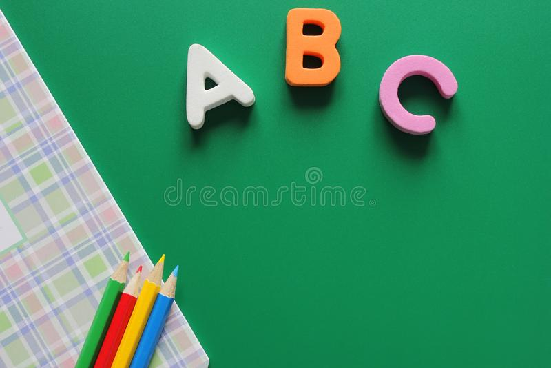 Erste Buchstaben ABCs-d des englischen Alphabetes auf einem grünen Hintergrund Schulnotizbuch und farbige Bleistifte Leerer Platz lizenzfreies stockfoto