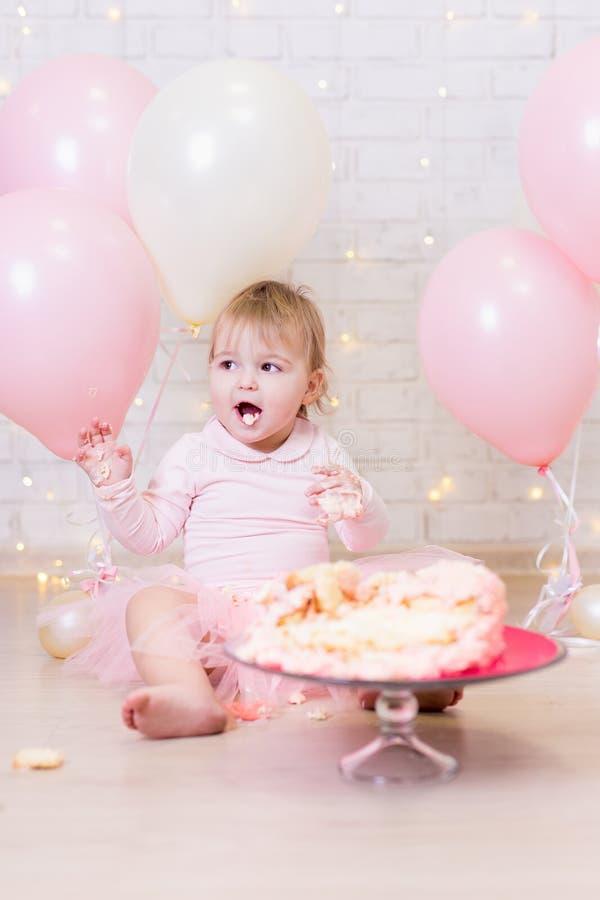 Erste Geburtstagsfeier - lustiges wenig Mädchen Essen und smashi lizenzfreies stockfoto