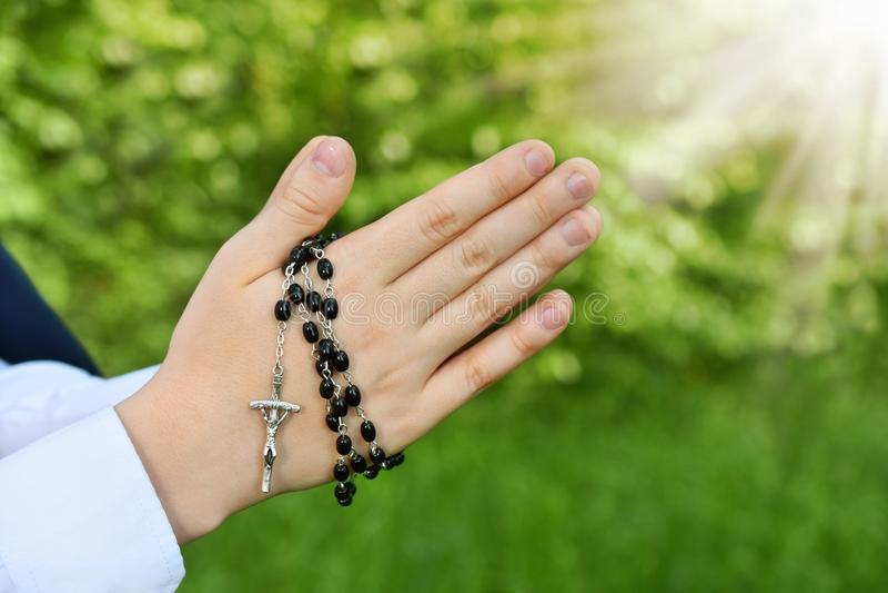 Erste heilige Kommunion mit Rosenbeet um betende Jungenhände stockbilder