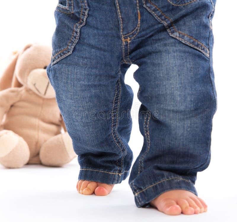 Erste Schritte - kleine Babyfüße in den Jeans lokalisiert auf Weiß mit lizenzfreie stockfotos
