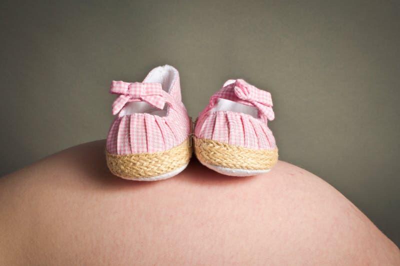 Erste Schuhe der Babys auf einem Stoß der schwangeren Frau stockfotos