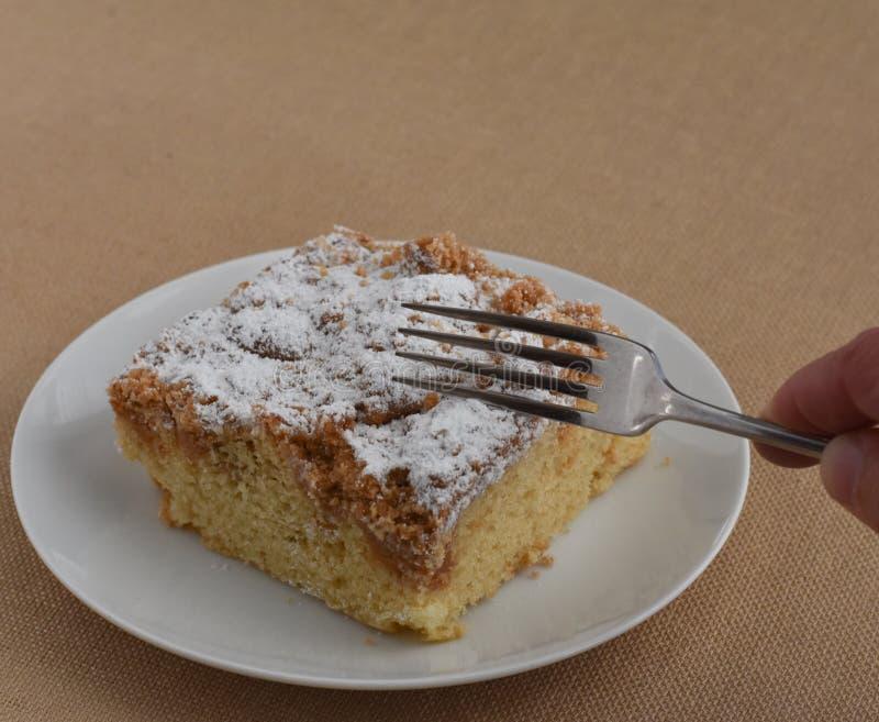 Ersten Biss von New York essend, reden Sie Streuselkuchen mit Gabel an lizenzfreie stockbilder