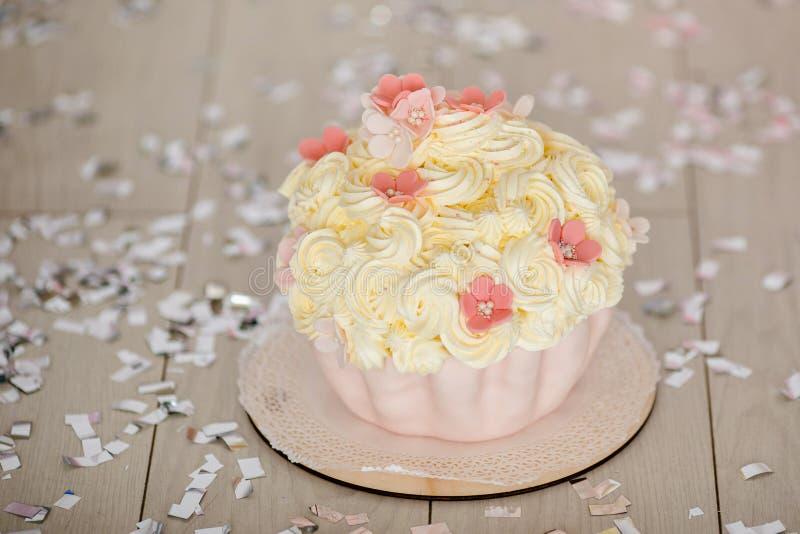 Erster Geburtstagsrosakuchen mit Blumen für kleines Baby und Dekorationen für Kuchenzertrümmern stockfotos
