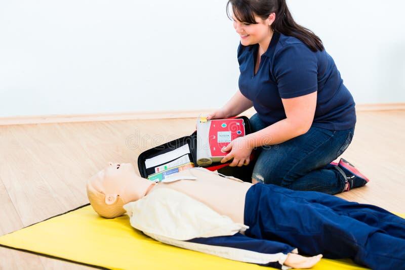 Erster Helferauszubildender, der Wiederbelebung mit Defibrillator lernt lizenzfreie stockfotos