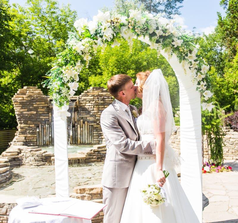 Erster Kuss eben des verheirateten Paars unter Hochzeitsbogen lizenzfreie stockfotografie
