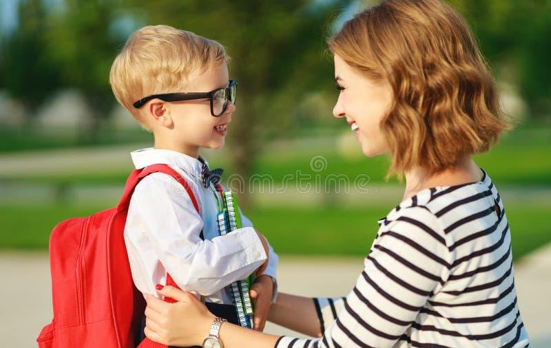 Erster Tag an der Schule Mutter führt kleines Kinderschuljungen im ersten Grad stockfotografie