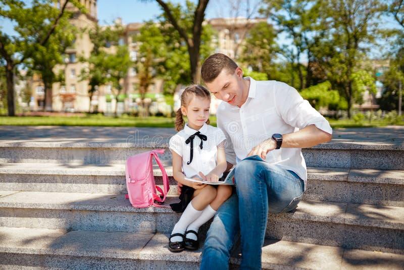 Erster Tag an der Schule Vater- und Kleinkindtochter, die auf Treppe und Buch, Studienlektionen lesen sitzt Elternschaft und Kind lizenzfreie stockfotografie