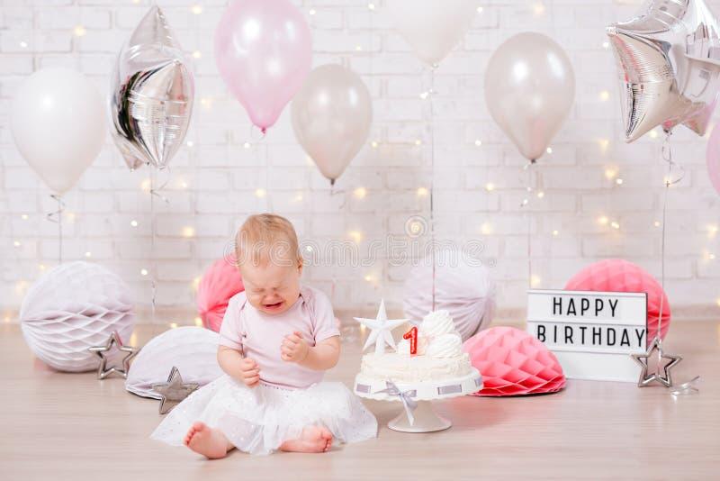 Erstes Geburtstagsfeierkonzept - trauriges kleines Mädchen, das mit Kuchen, Ballonen und Geburtstagsdekorationen schreit lizenzfreies stockbild