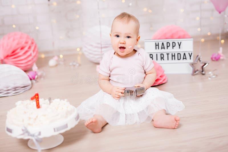 Erstes Geburtstagskonzept - Porträt des netten Babys und des zertrümmerten Kuchens mit Dekorationen stockfotos
